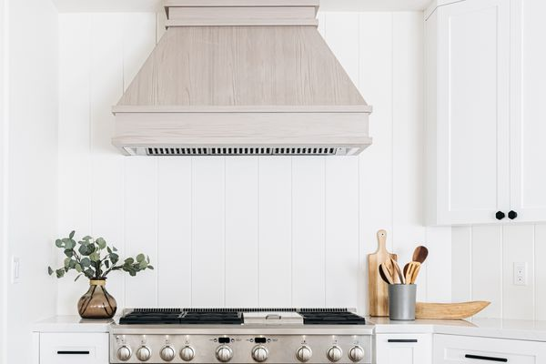 Kitchen backsplash with white boarding behind light wood-colored oven and ventilator