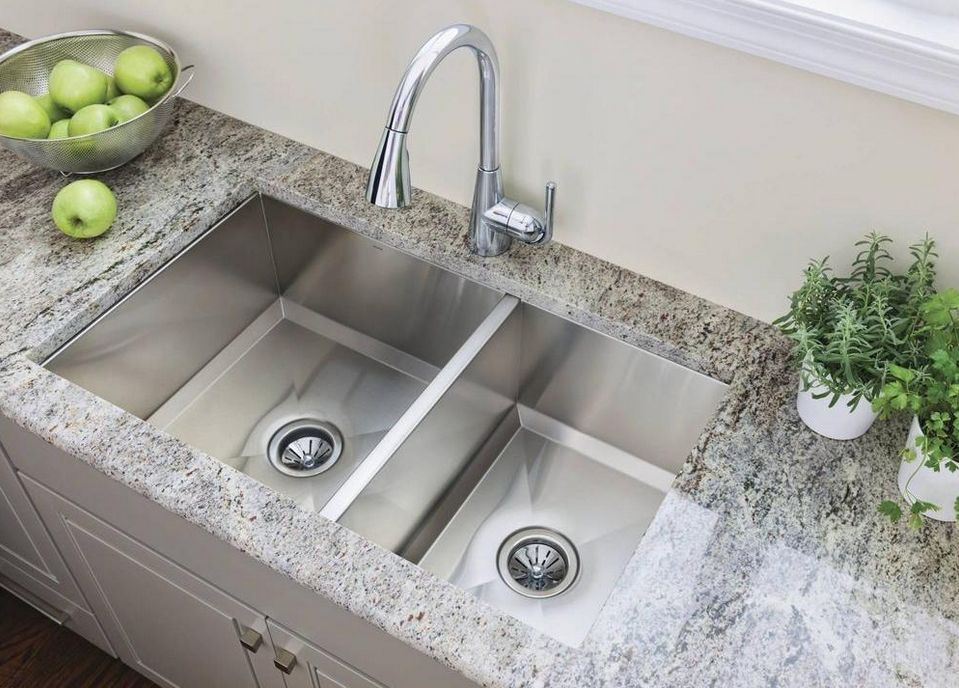 Moen 1600 Series stainless steel sink with marble counter, green apples in a bowl, and herbs in a pot on the counter.