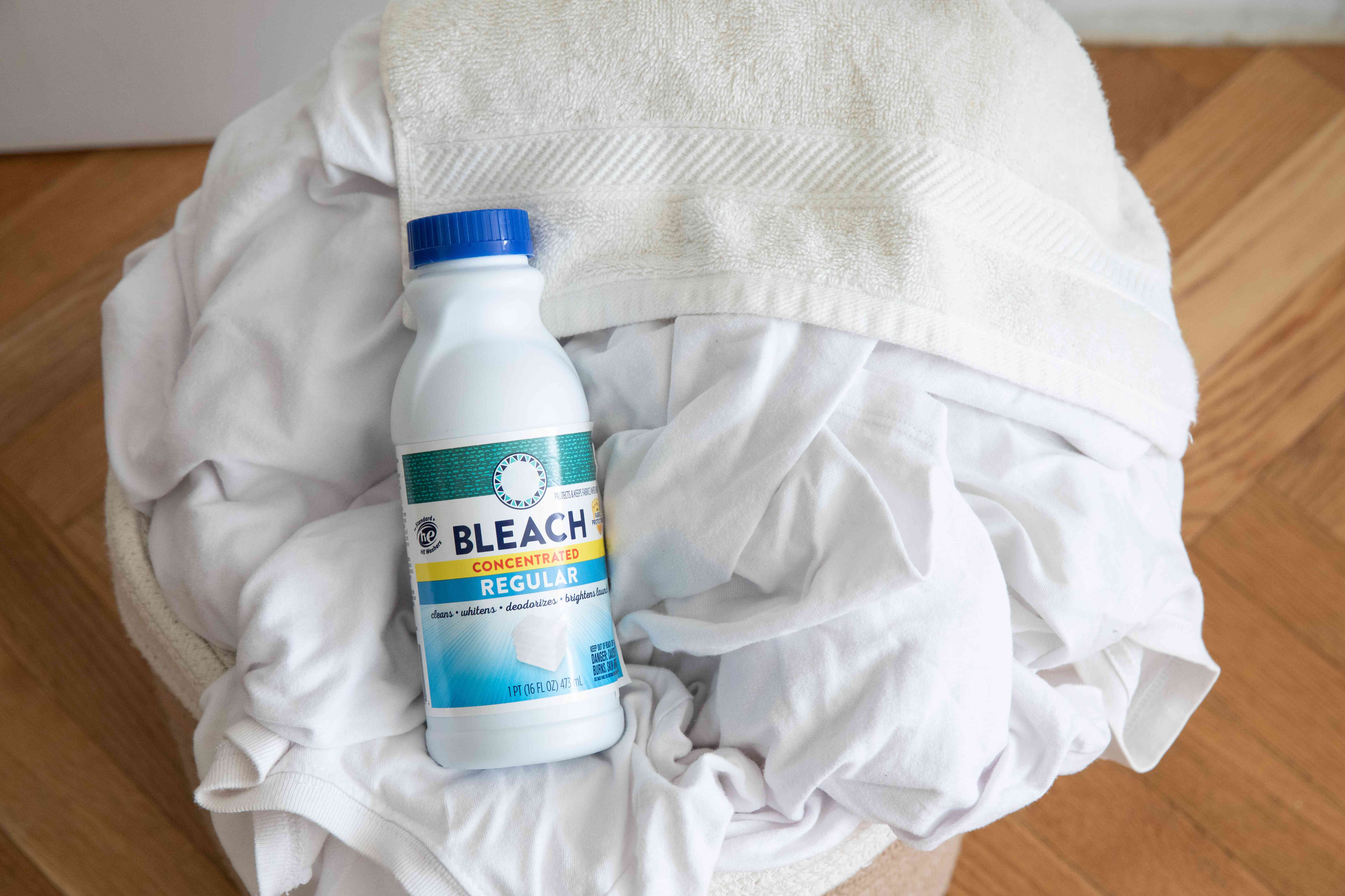 Chlorine bleach bottle on pile of white clothes and blankets