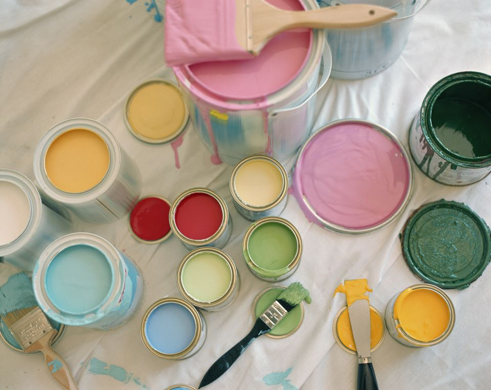 Different colors of paints in cans on a white drop cloth with paint brushes and lids
