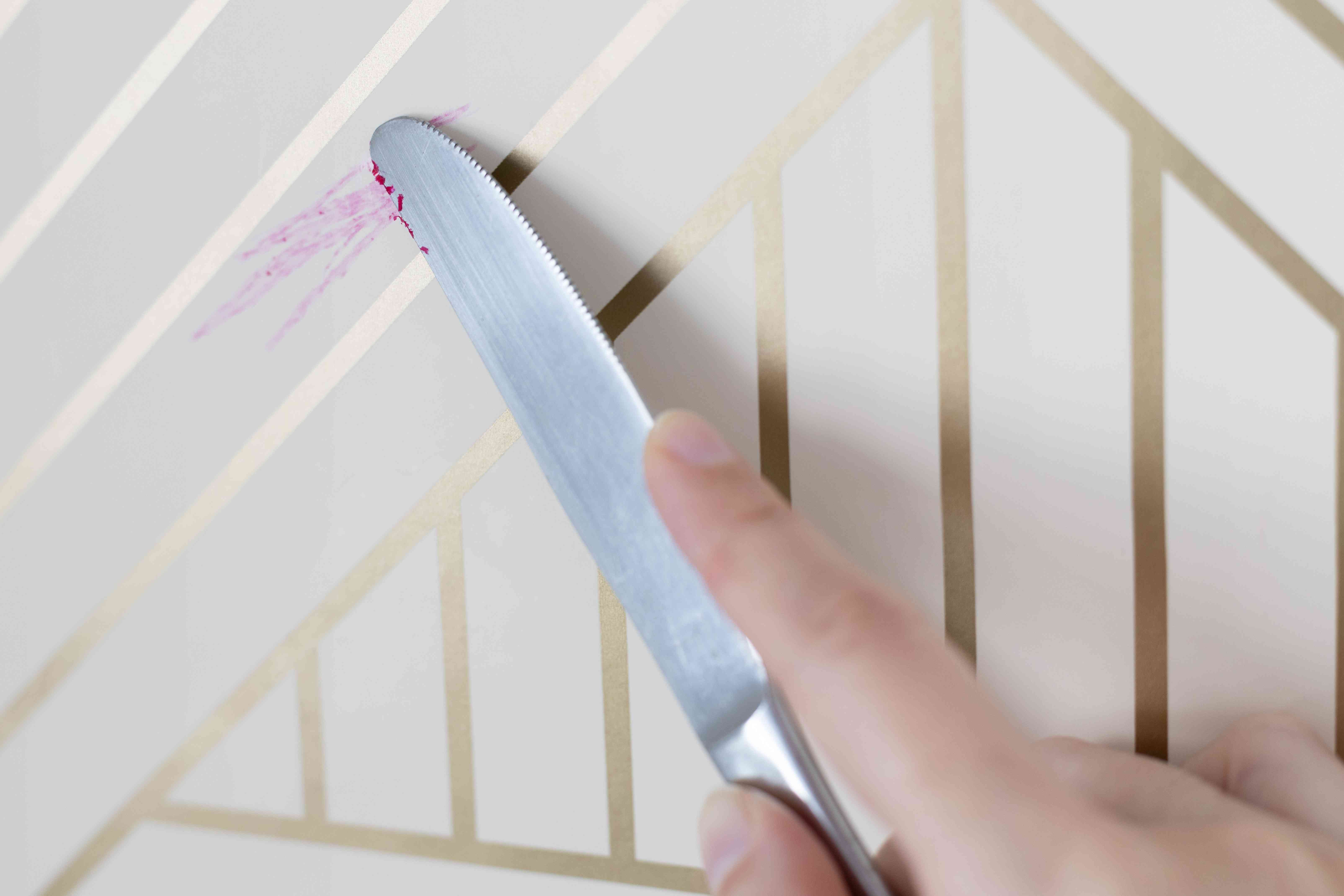 Pink crayon marks removed by dull-edged knife from what and gold striped wallpaper