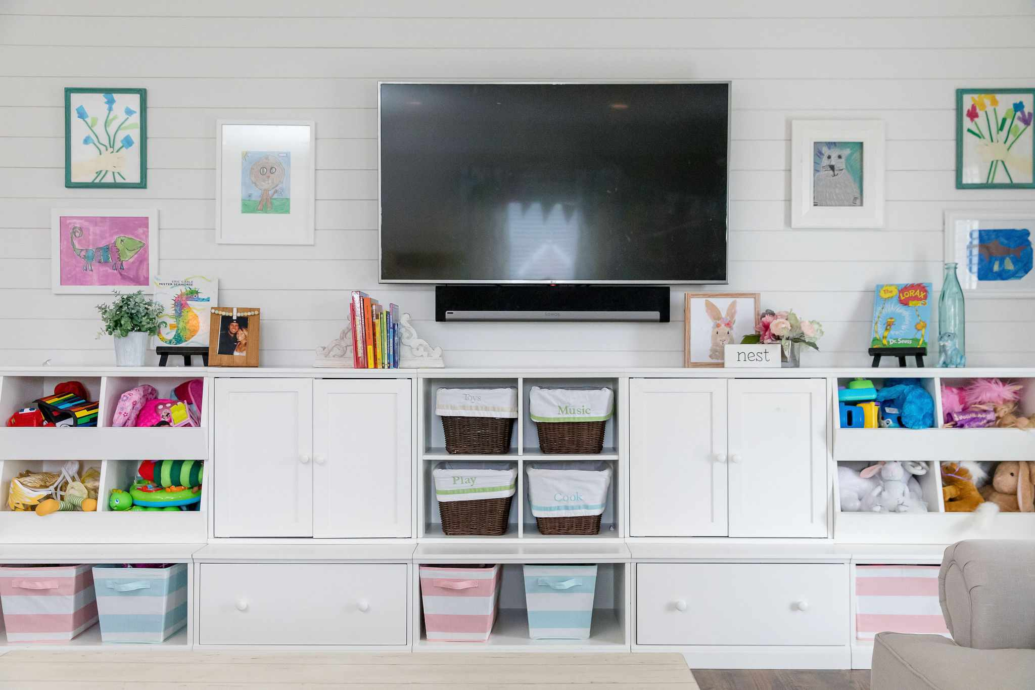 Color playroom with white cabinetry and wall-mounted television by Jenny Reimold