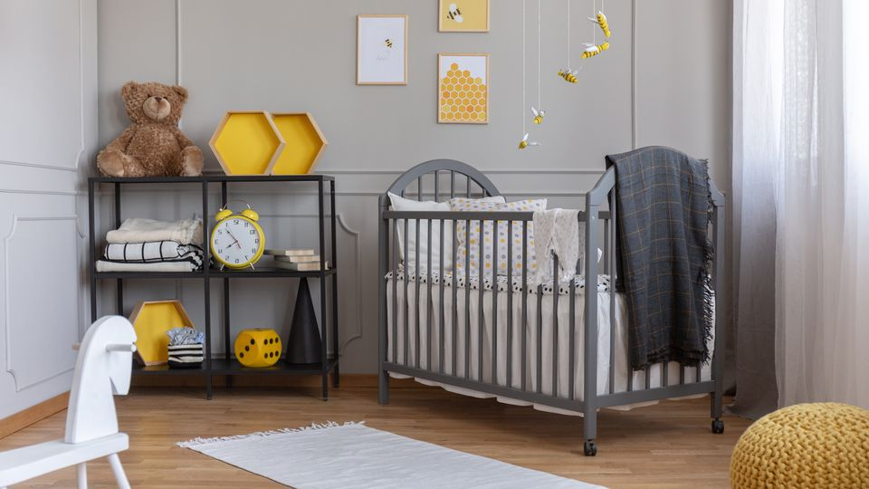 Installation with yellow and black bees above grey wooden crib with blanket and pillow