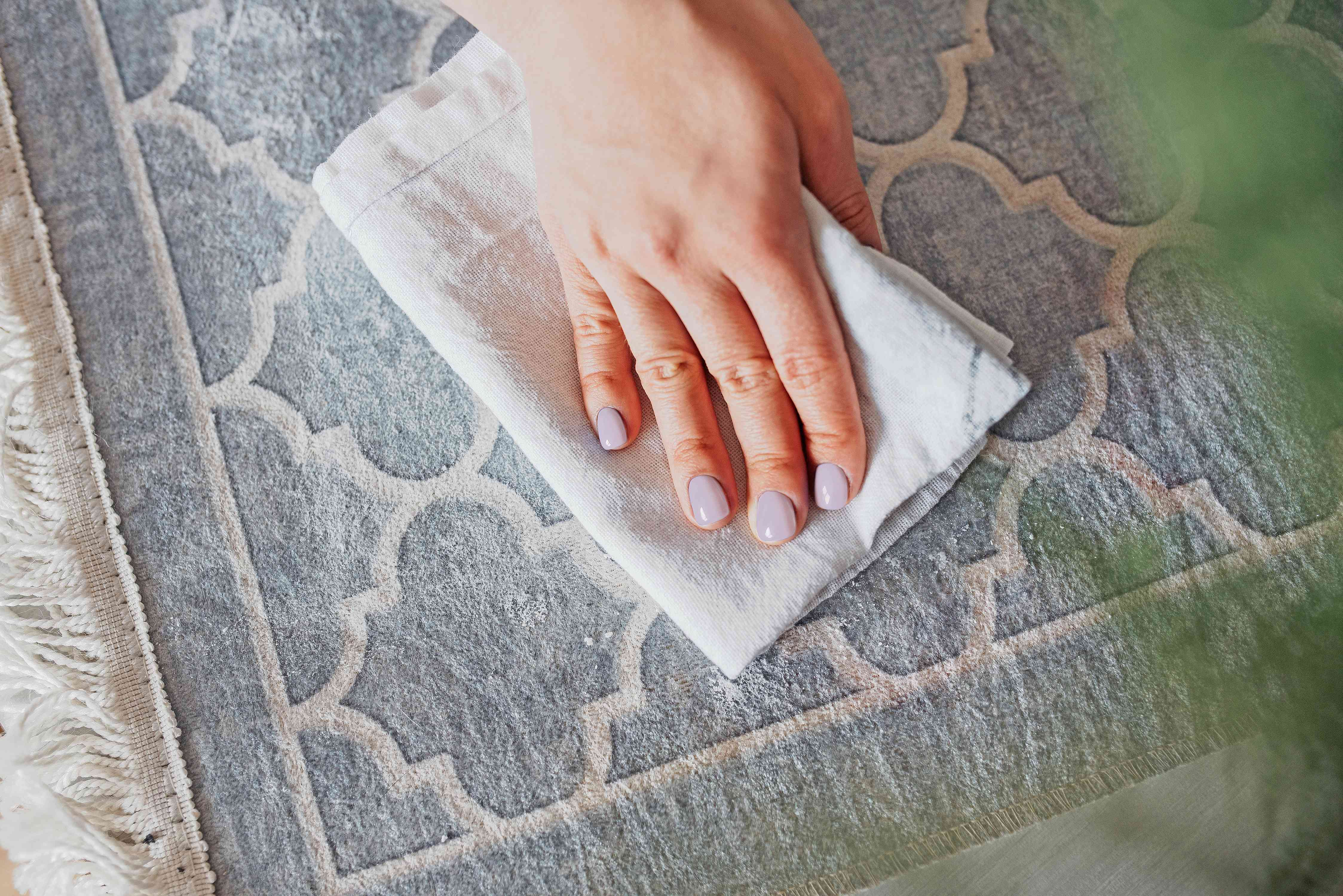 Correction fluid stain on gray carpet blotted with white cloth