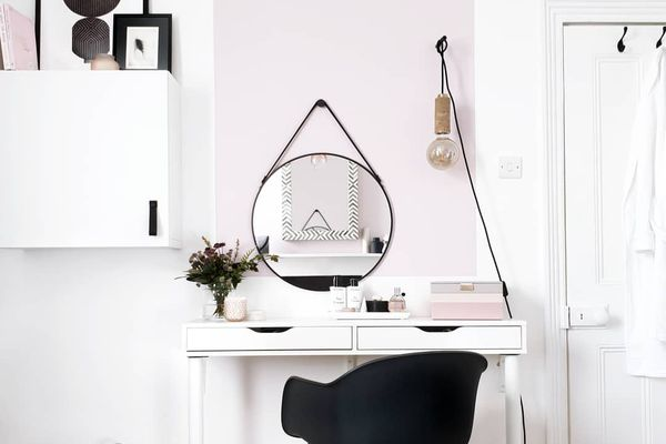 white desk with a black chair and a basket underneath