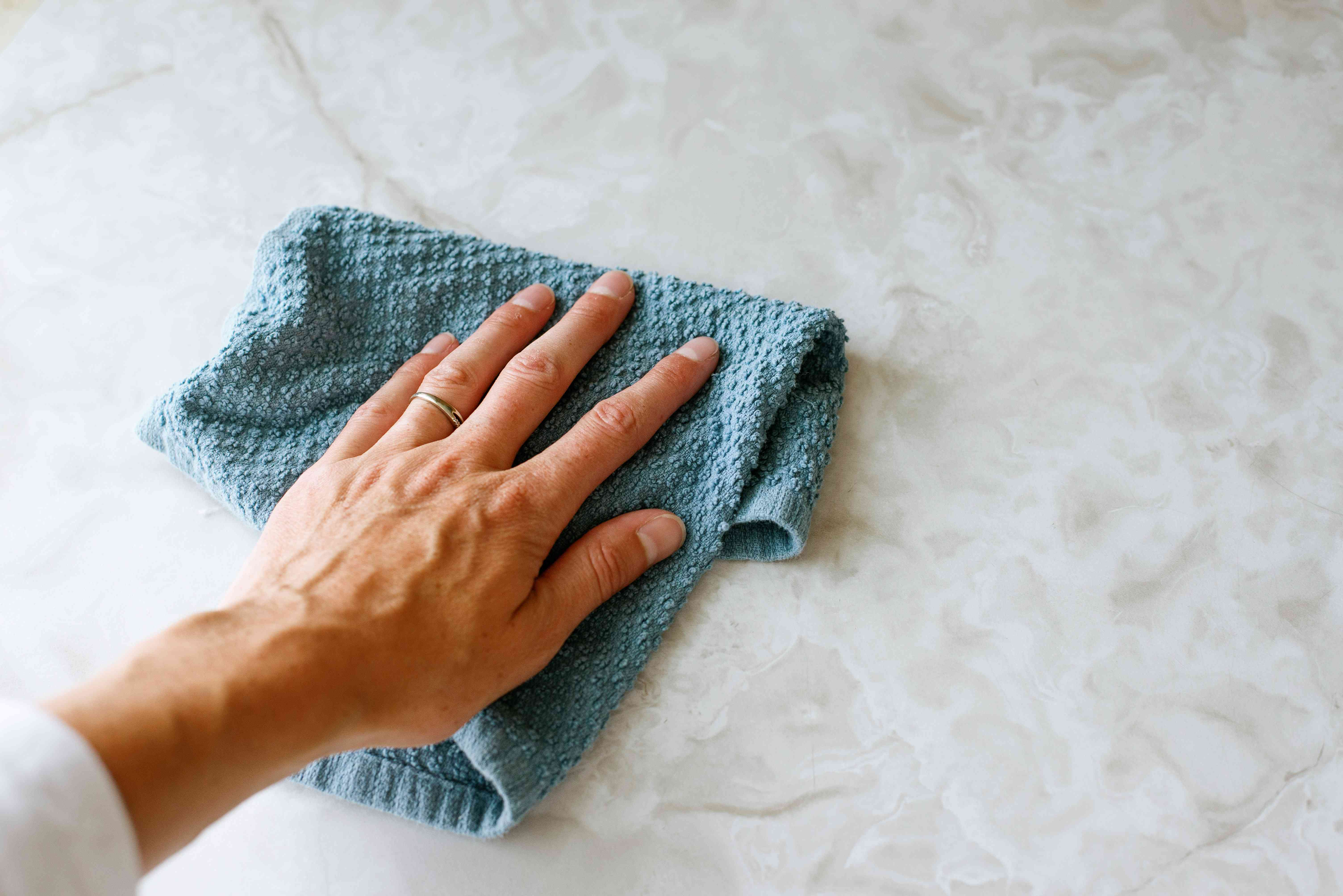 Old blue rag wiping down washing machine before using