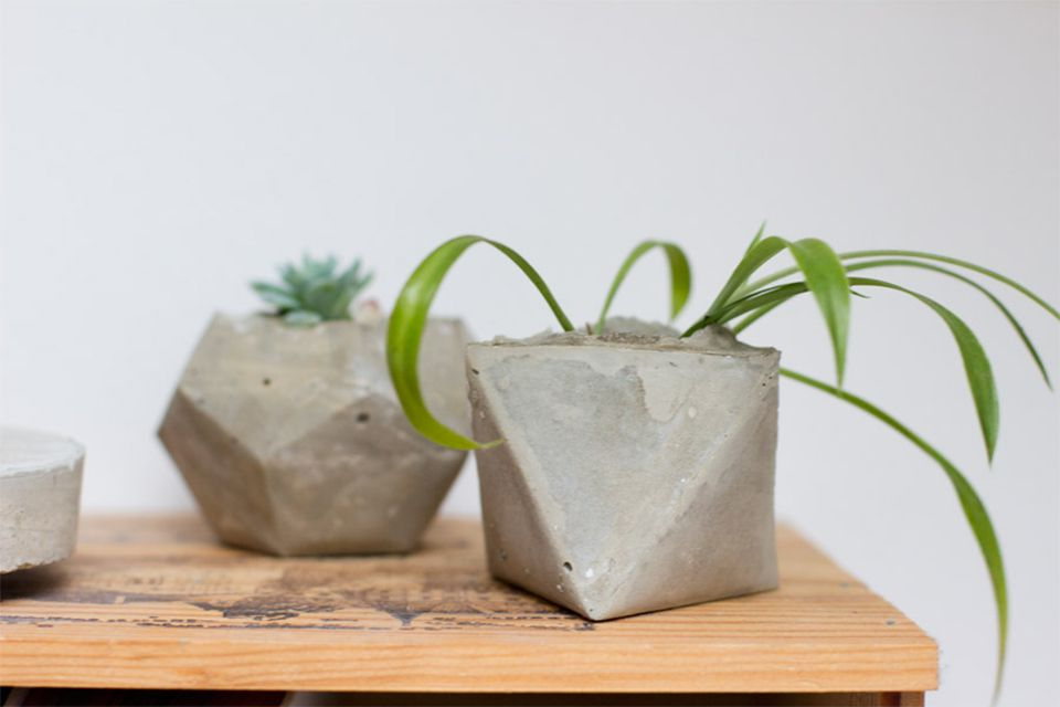 Two geometric concrete planters on a table