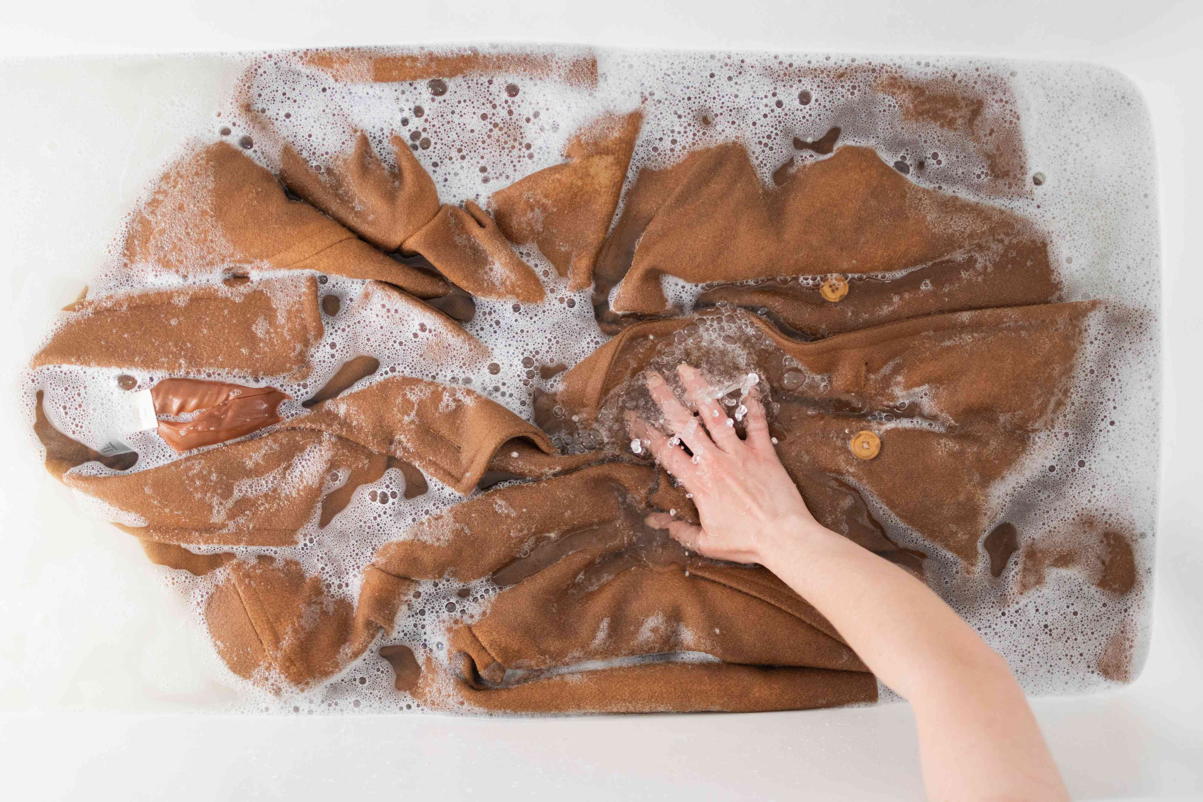 Tan wool coat agitated by hand in tub of water and wool wash solution
