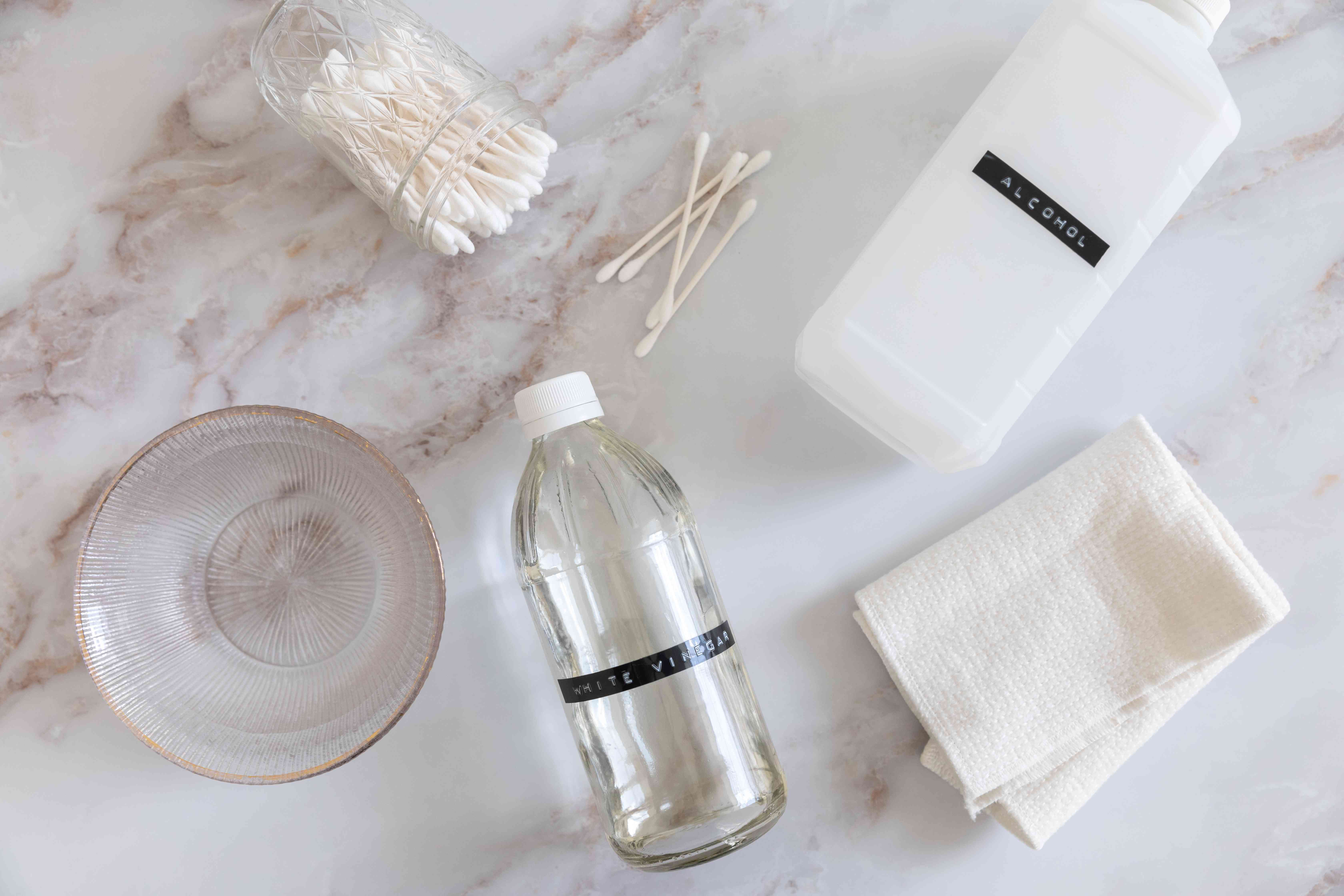 Materials and tools to deep clean oil diffuser on white marbled surface