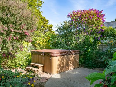 Hot tub in garden of home during the day with no people: closed cover
