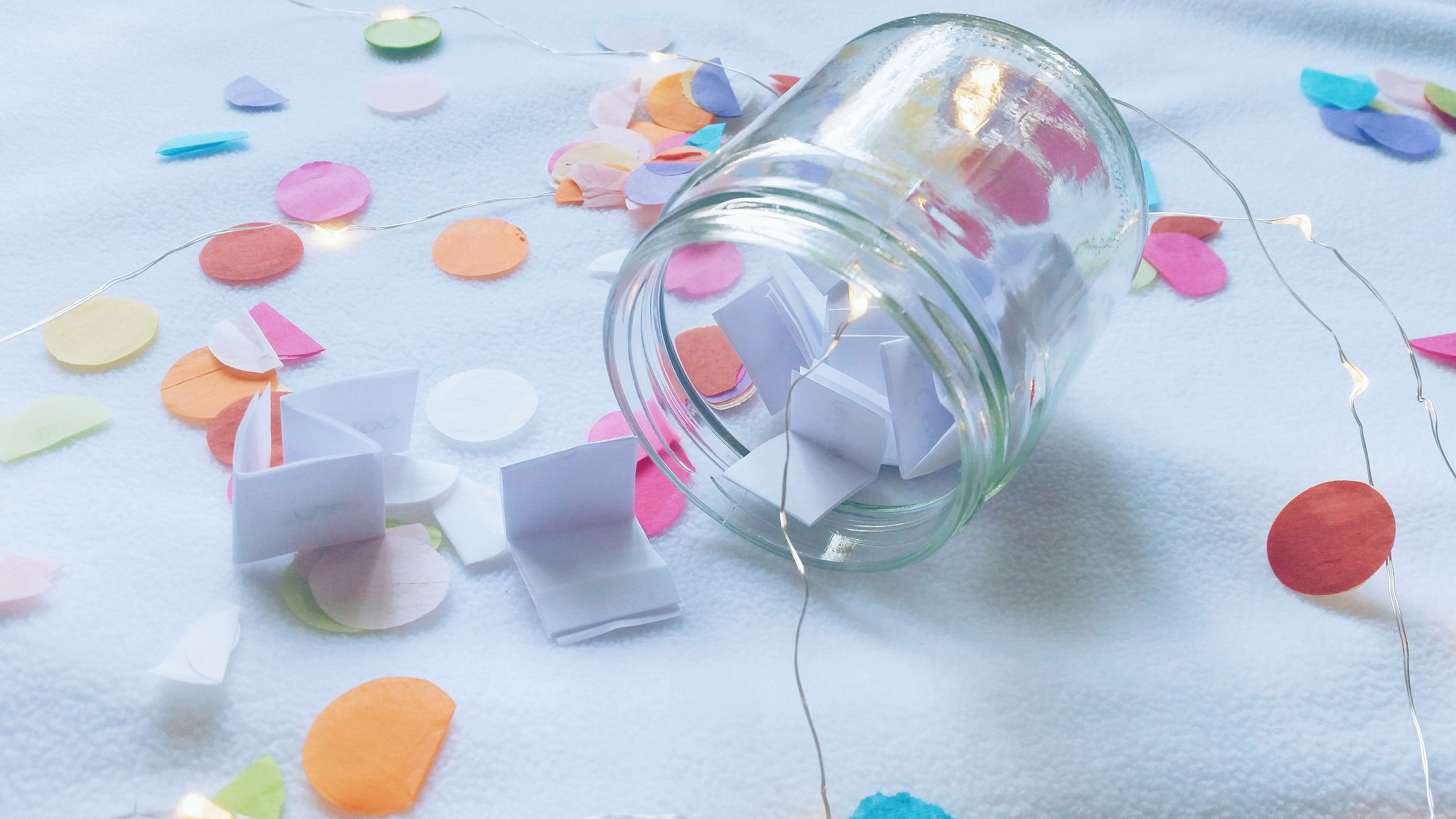 Glass wish jar filled with paper wishes on a table with confetti
