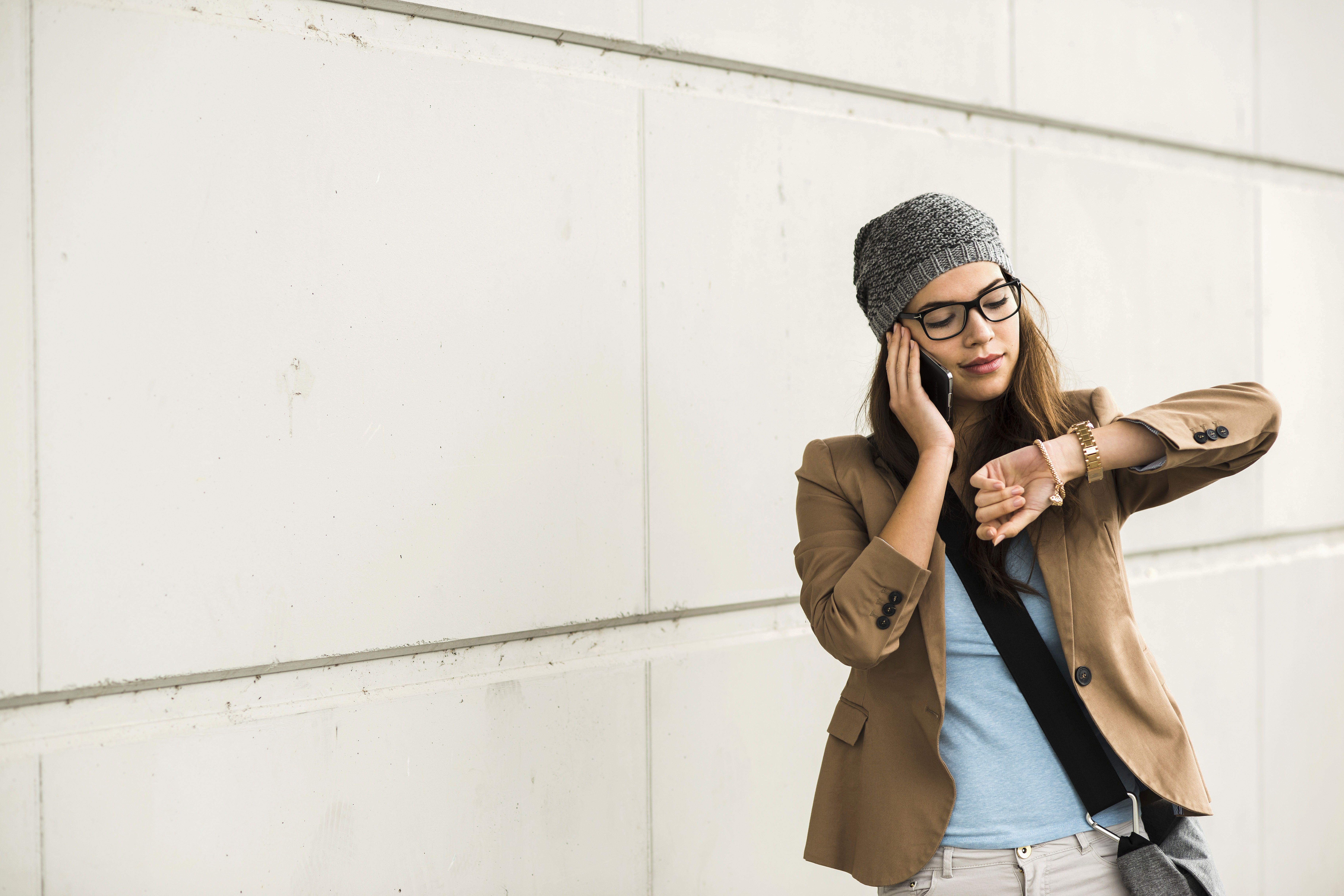 Mujer joven que llama por teléfono con un teléfono inteligente mientras verifica el tiempo