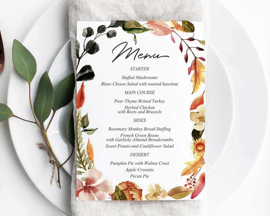 A menu on a plate with fall leaves and florals