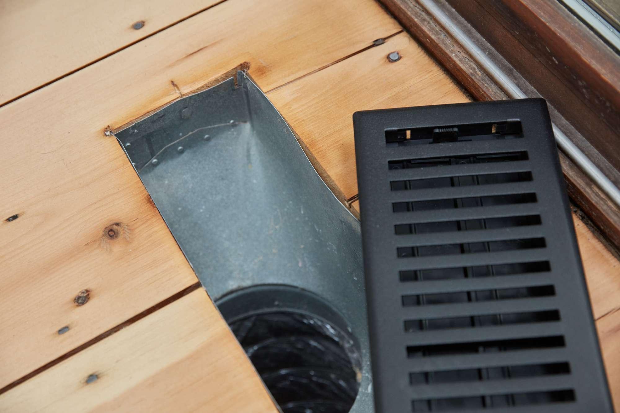 Exposed floor HVAC vent in wood flooring