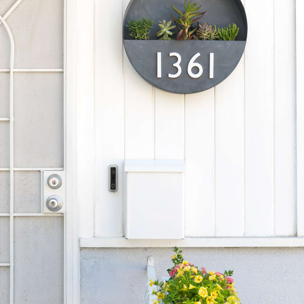 A round metal planter box with address numbers.