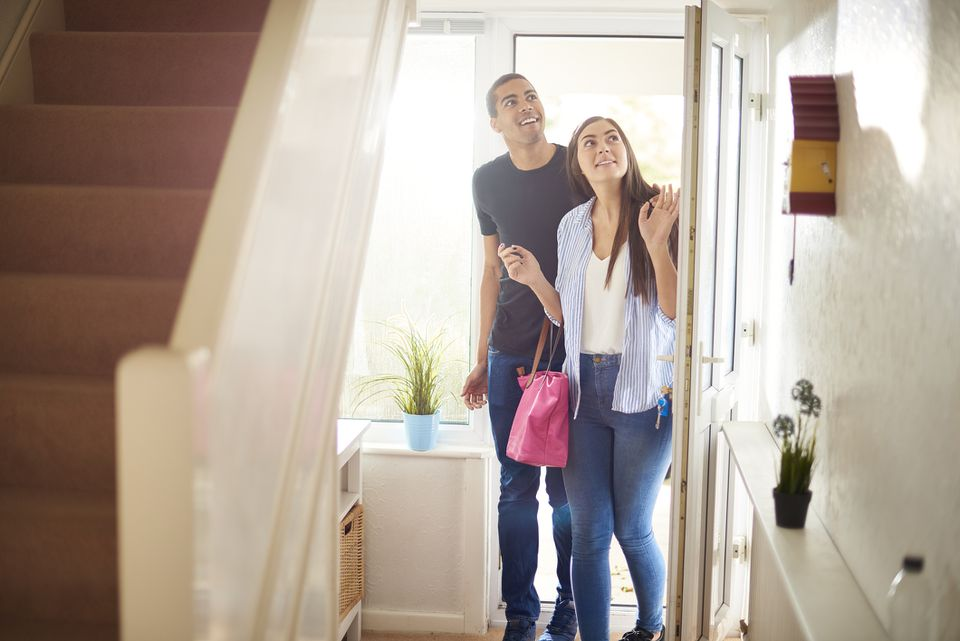 Young couple stepping into a small foyer at house viewing