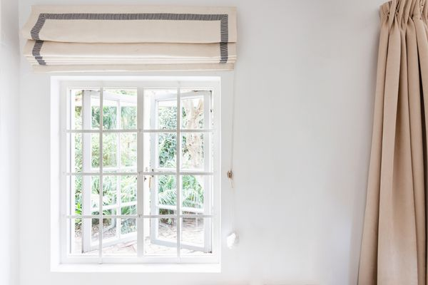 Window with white pane and folded cream and gray blinds above and tan curtain on the side