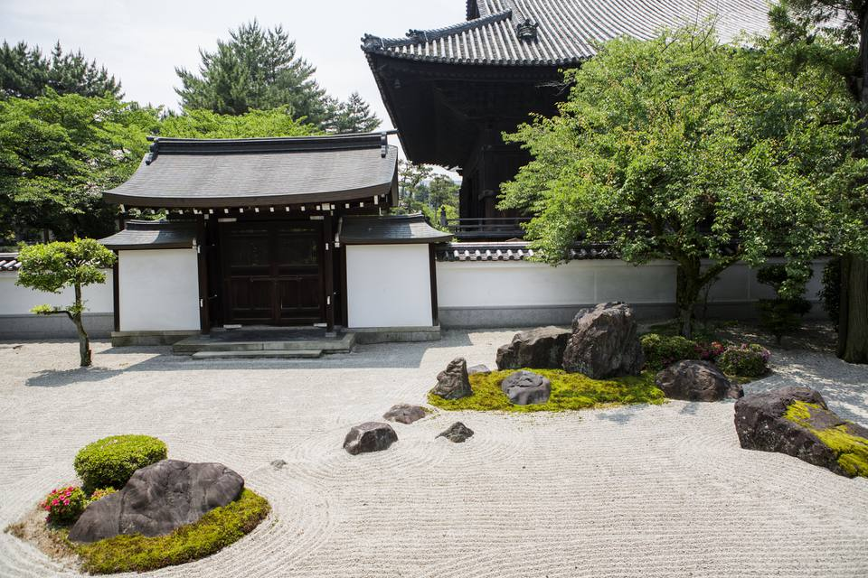 Zen garden with plants and Japanese structures.