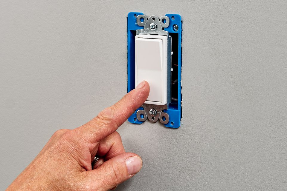 Newly installed light switch being tested by hand