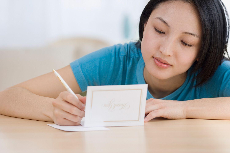 woman writing thank you card