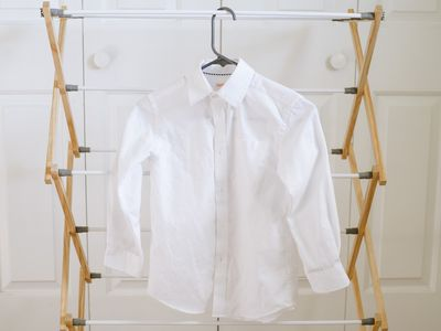 White button-down shrunken shirt hanging on drying rack