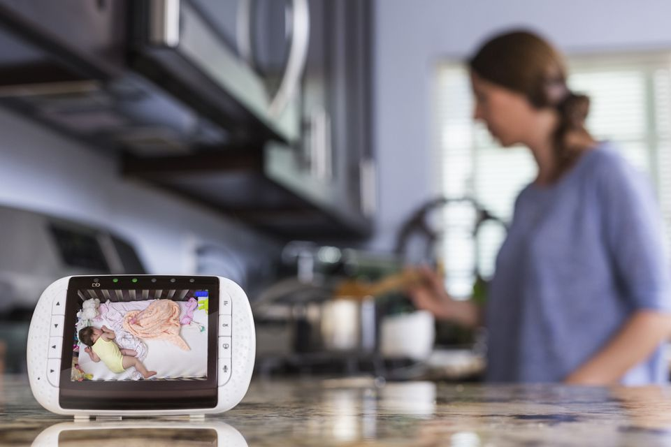 Close up of baby monitor in kitchen with woman cooking in background.