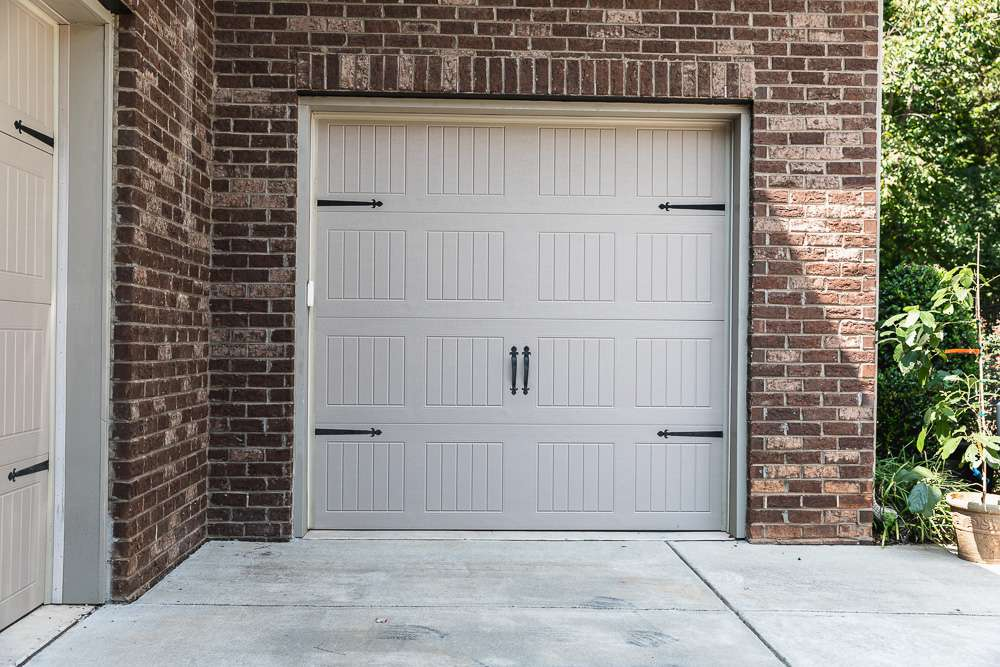 Tan garage door remaining closed and surrounded by brick wall