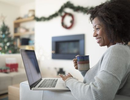 Smiling woman using laptop and drinking coffee on sofa in Christmas living room