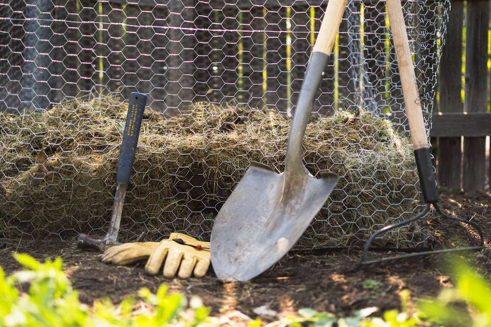 Homemade composter in wired fencing next to shovel, rake, garden gloves and hammer in backyard