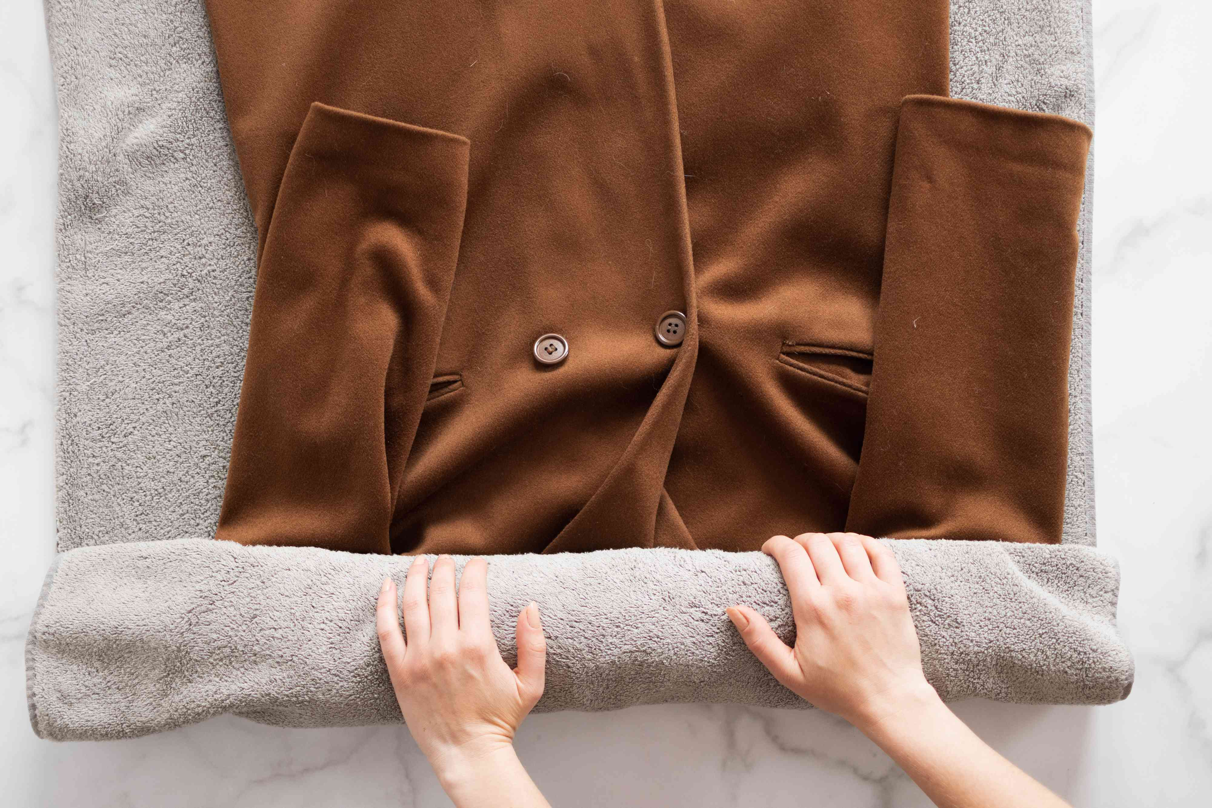 Brown wool coat rolled into gray towel to air dry flat