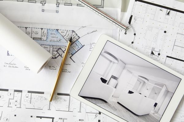 Architectural blueprints and digital tablet displaying modern showcase interior