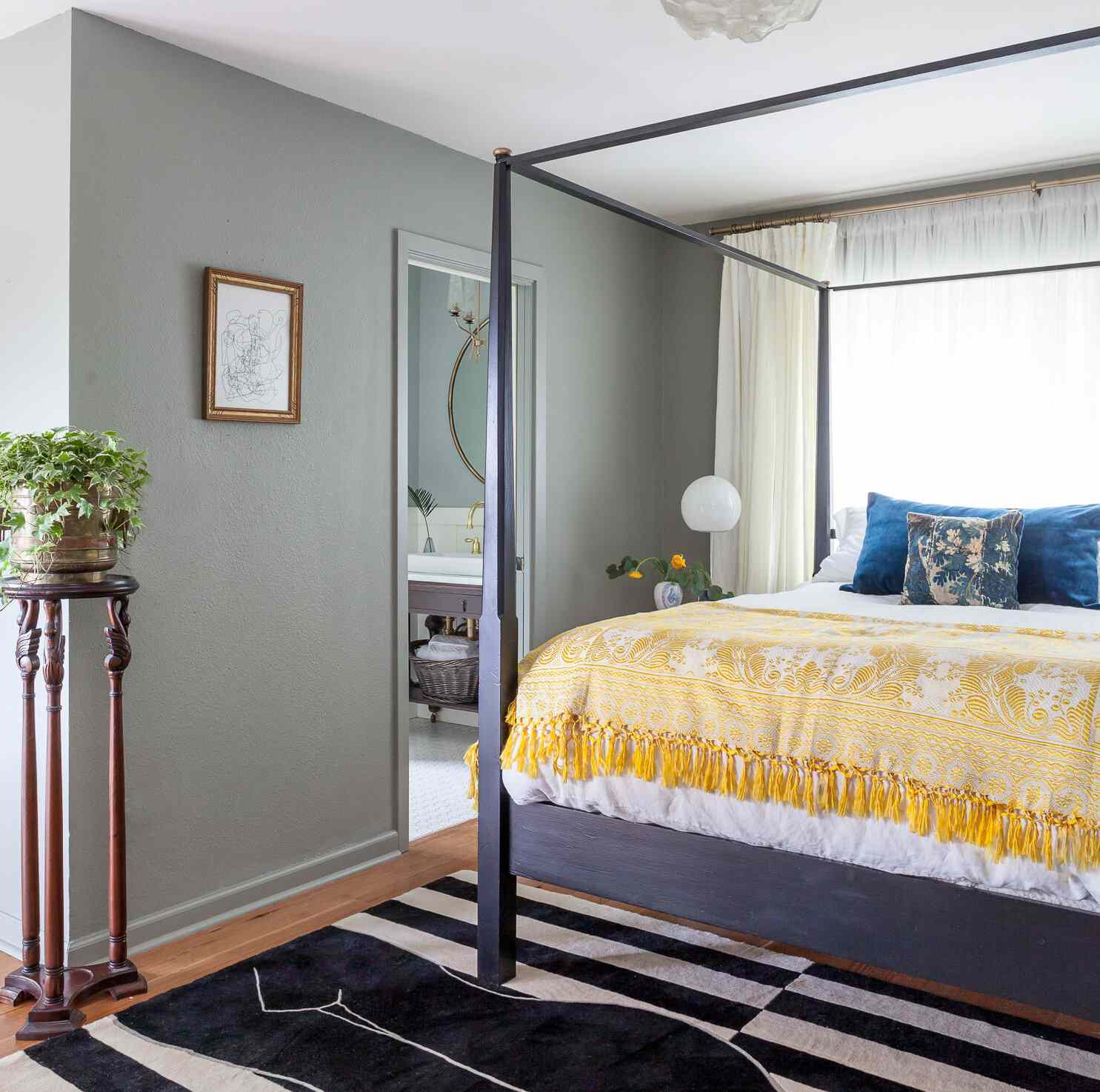 bed with four poster frame, blue and yellow bedding, gray walls