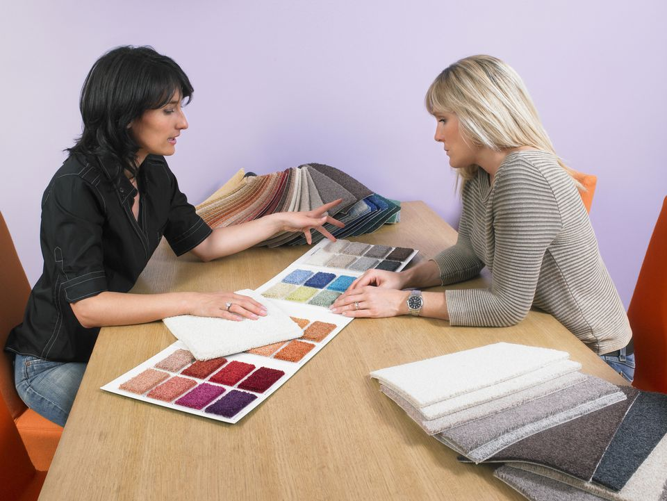 Designer showing carpet samples to client.