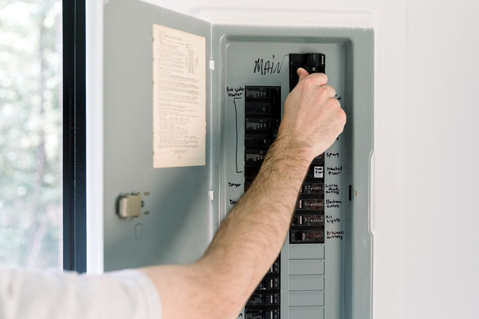 person switching a main breaker