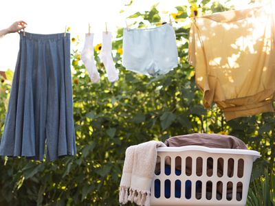 Basket of laundry in front of clothes line with clothes hanging to air dry
