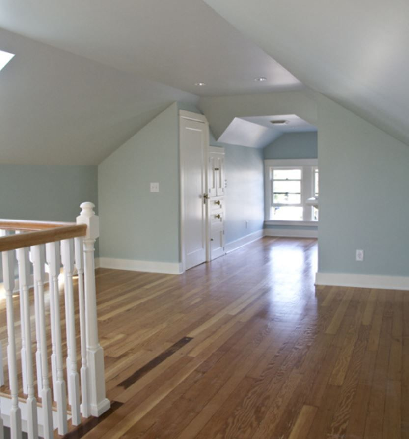 Updated attic space with wood floors and light blue walls.