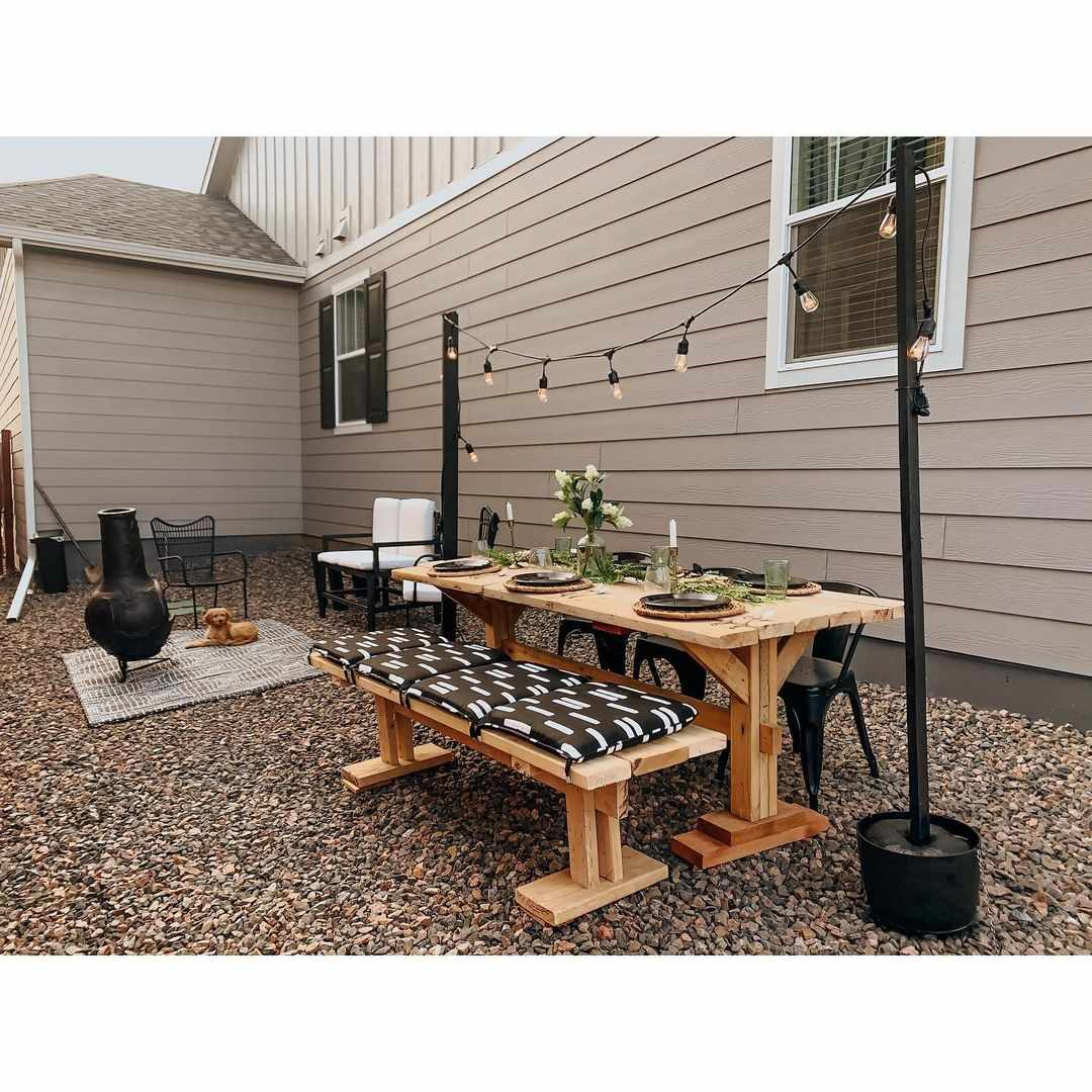 A gravel backyard with a picnic table set up for al fresco dining.