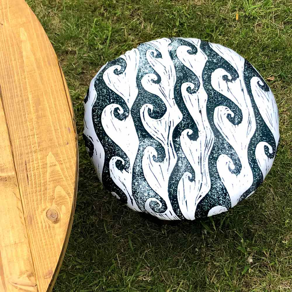 A stool covered with fabric sitting on the grass