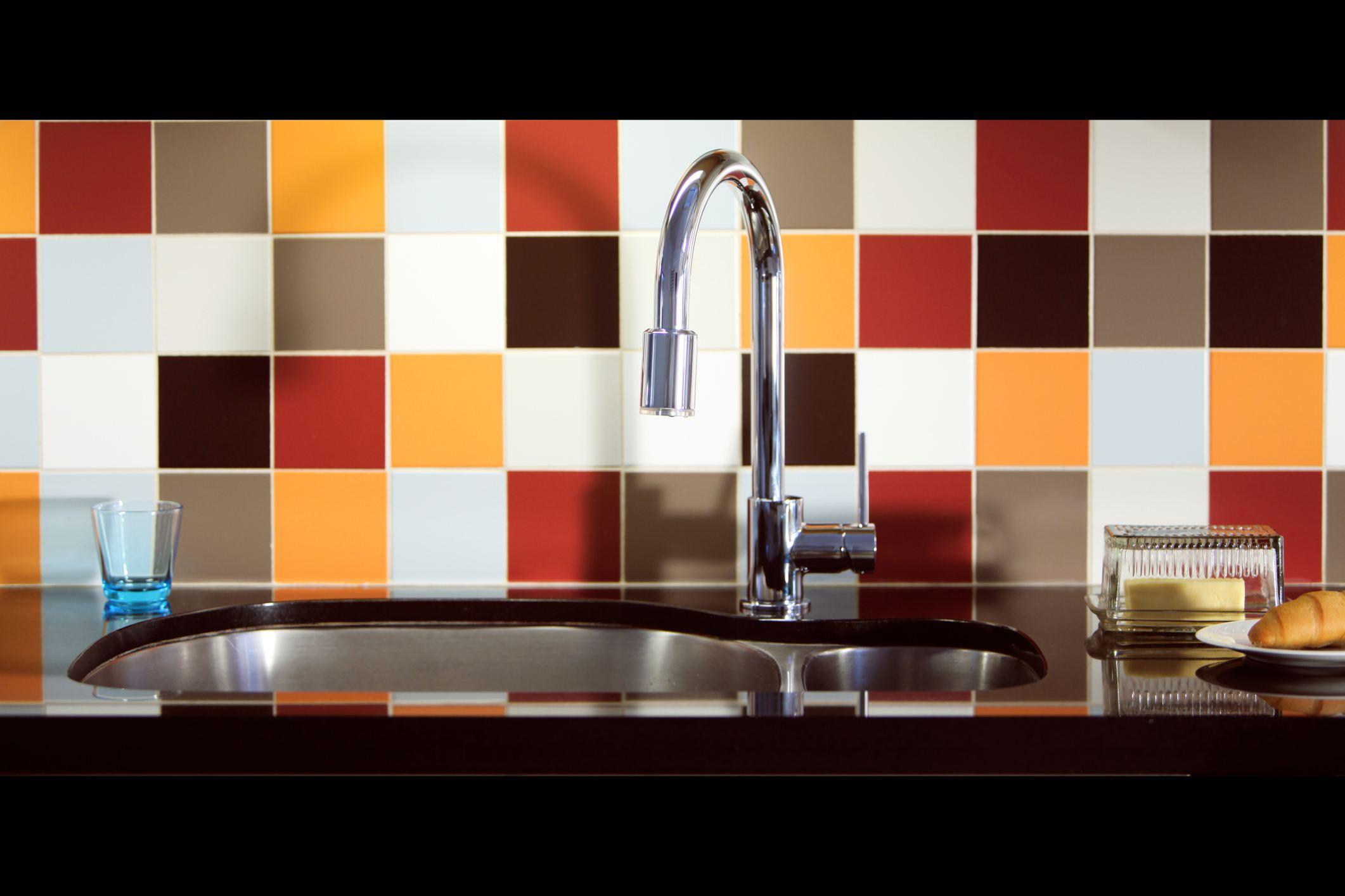 Multi Colored Tile Backsplash Behind Sink in Kitchen 146638780