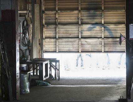 A garage door opening, revealing people beyond it