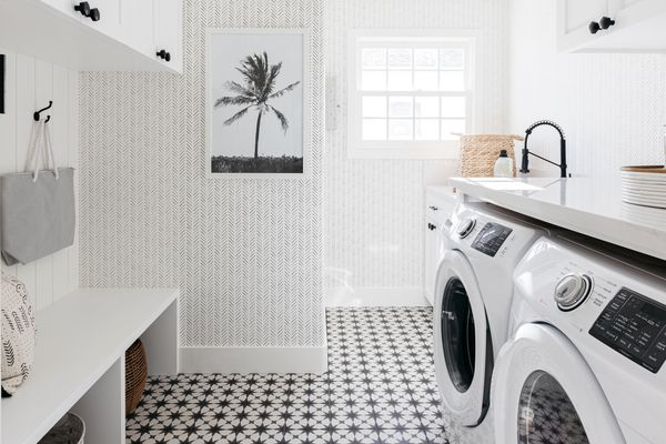 Laundry room with and black and white patterned flooring and decor items across laundry machines