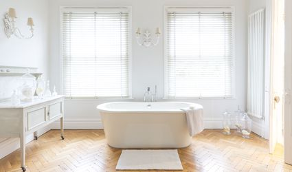White, luxury home showcase bathroom with soaking tub and parquet hardwood floor