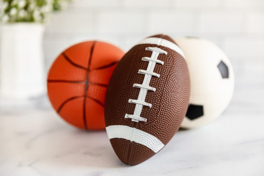 Small football, basketball and soccer ball on white surface to sell for cash