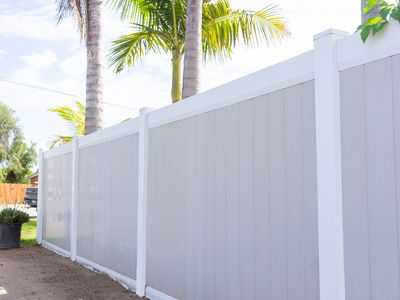 Gray and white vinyl fencing in front of palm trees and yard