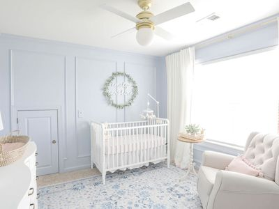 nursery with pale blue walls and white furiture
