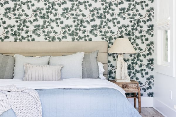 Wallpaper design with vines and leaves behind bed with white, gray and blue bedding
