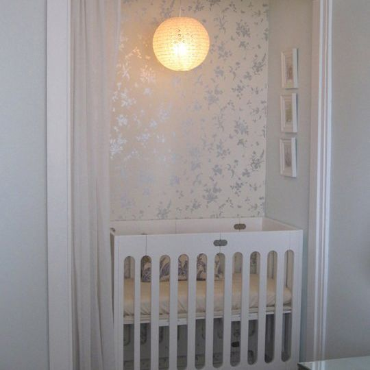 Closet nursery with curtain and wallpaper accent wall