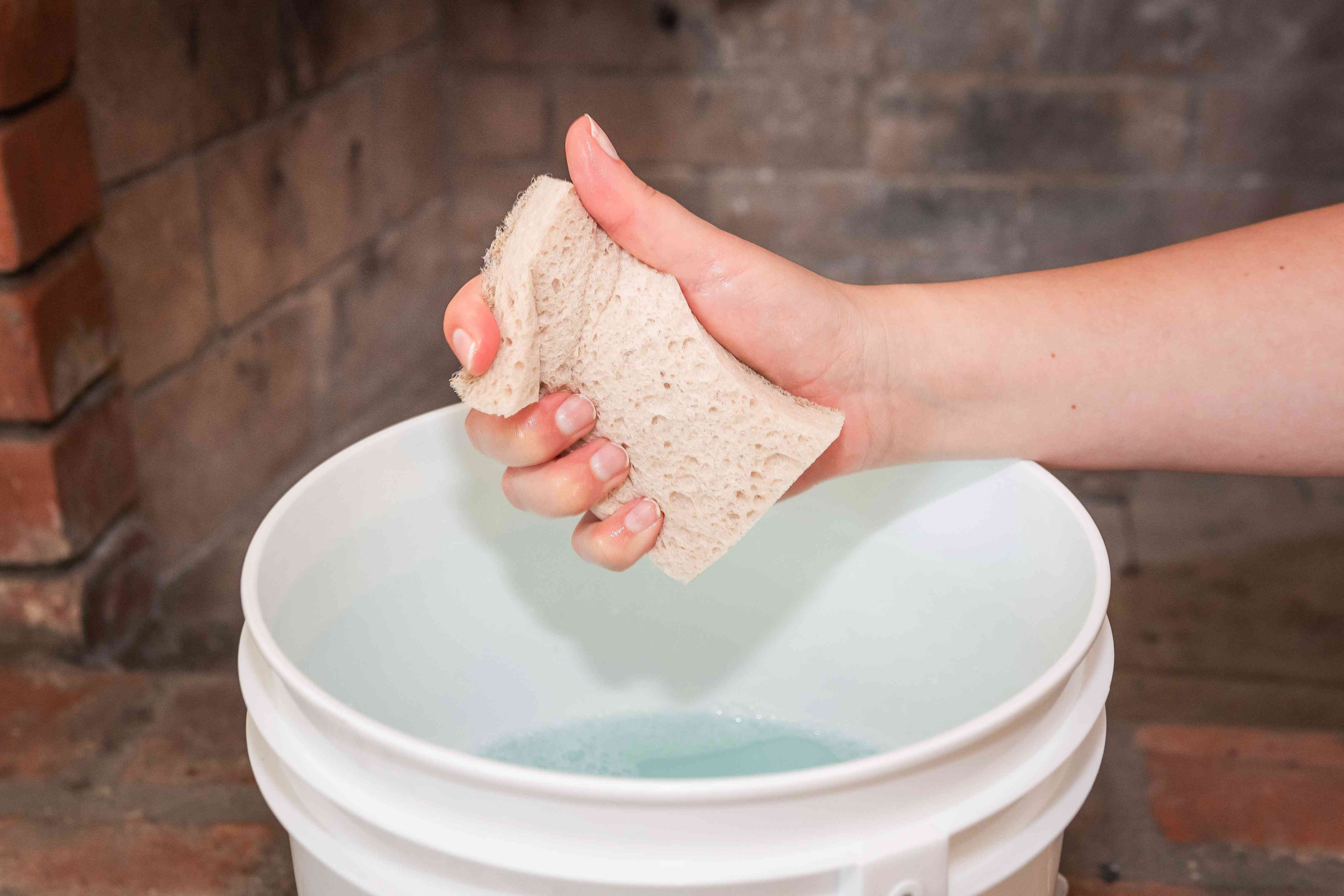 Sponge squeezed over bucket with water and vinegar solution to rinse fireplace