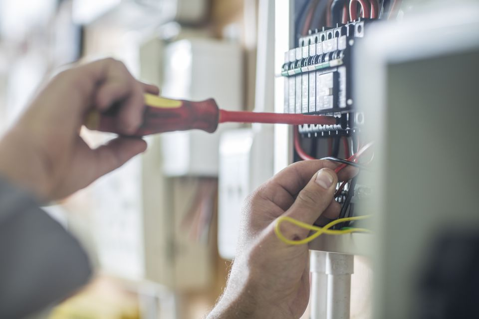 Electrician working on wired electrical board