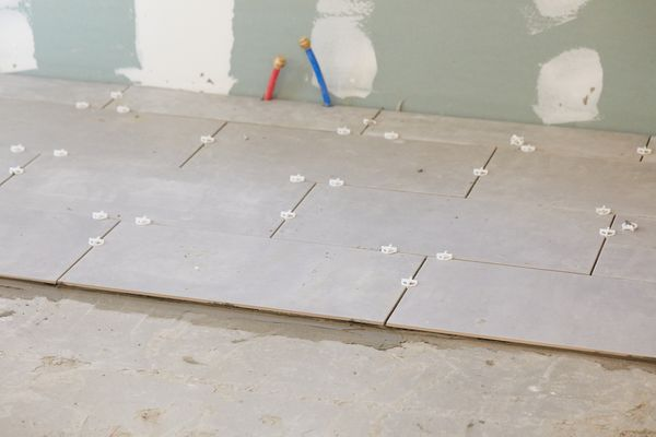 Kitchen flooring being installed with ceramic tiles in renovated room